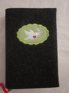 Taubenbutton grün auf dunklem Filz